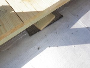 Wooden roof deck resting, directly, on the roof membrane