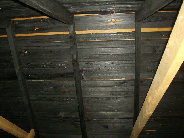 Fire damaged rafters and roof deck planks.  Incomplete and cheap repair after a fire.