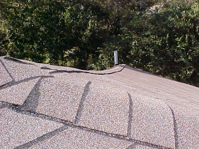 Sagging roof ridge cause by cracked ridgeboard.