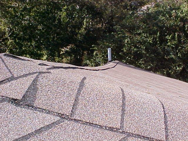 Sagging roof ridge cause by cracked ridgeboard.